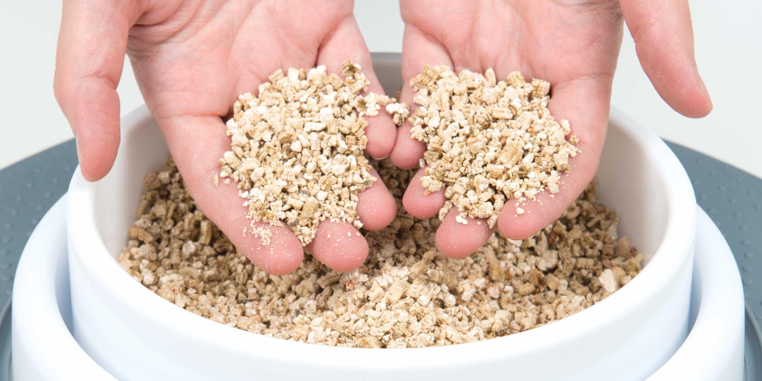 Hands holding up vermiculite for the grass planter